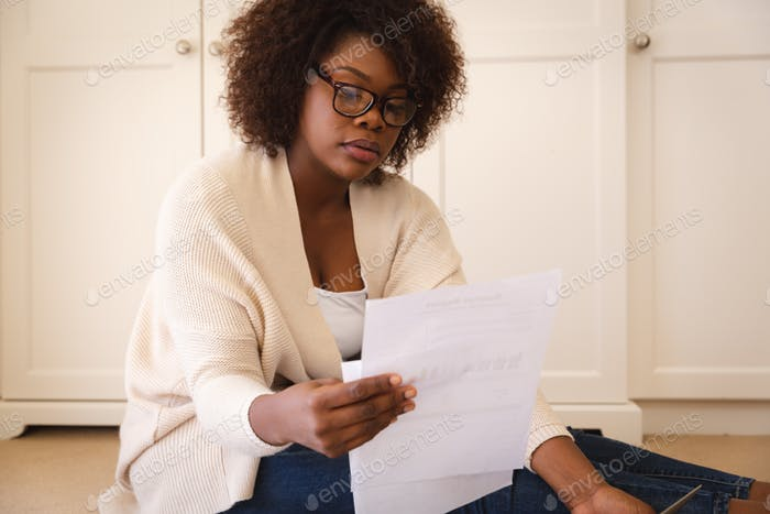 Happy african american woman working in bedroom, sitting on floor and reading paperwork