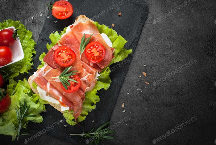 Ciabatta sandwich with  salad leaves jamon serrano mozzarella on