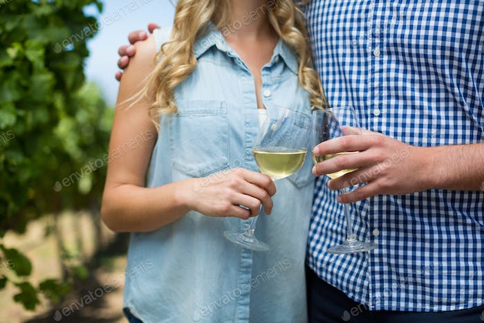 Mid section of couple holding wineglasses
