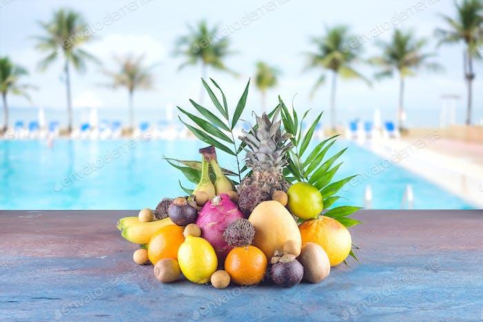 Verschiedene tropische Früchte am Strand Orange, Ananas, Limette, Mango, Drachenfrucht, Orange, Banan