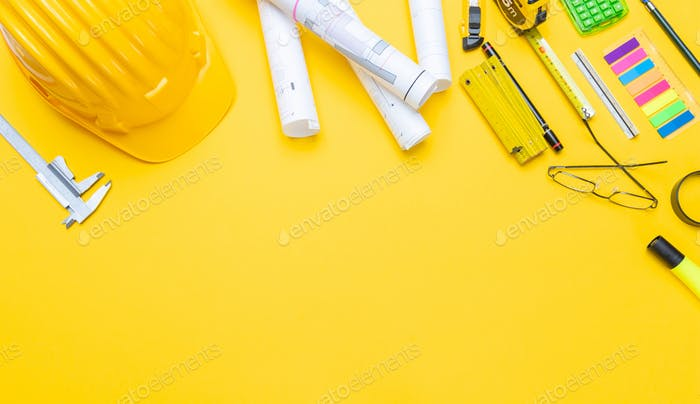 Project blueprints, hardhat and engineering tools on yellow