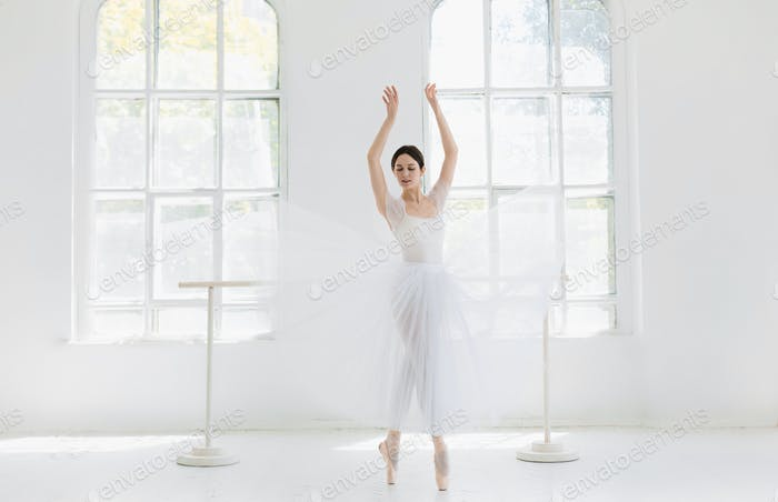 Young and incredibly beautiful ballerina is posing and dancing in a white studio