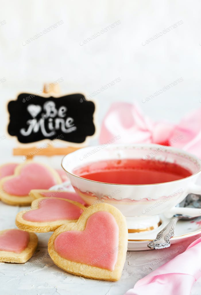 Heart shaped shortbread cookies and cup of red tea, Valentine co