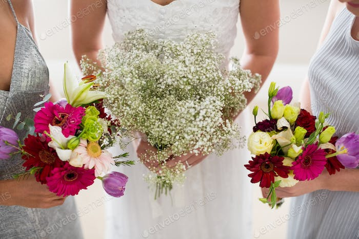 Mid section of bride and bridesmaids standing with bouquet