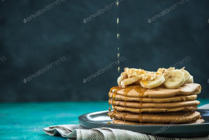 Gießen Ahornsirup über Pfannkuchen Haufen