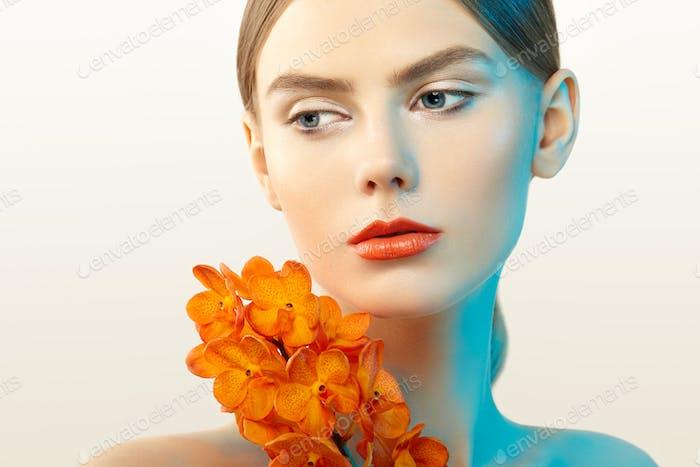Porträt von schönen jungen Frau mit Orchidee