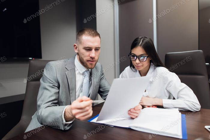 Female worker showing papers to her serious boss in the meeting room