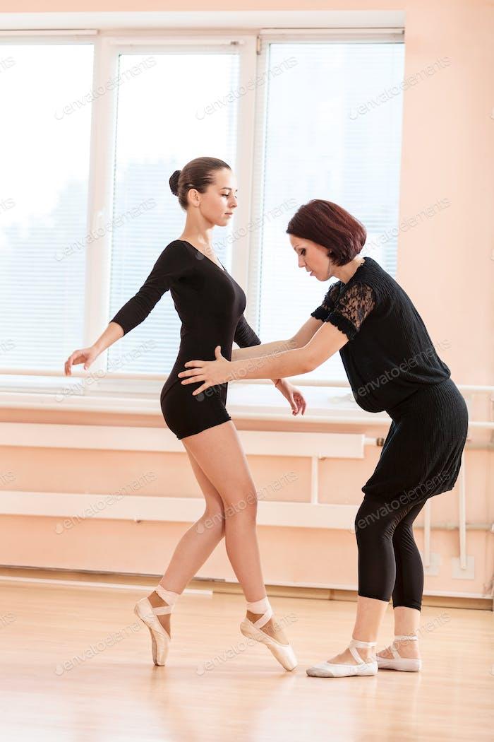 Ballet teacher and young girl at dance class