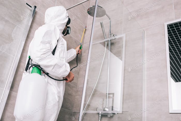 low angle view of pest control worker spraying pesticides with sprayer in bathroom