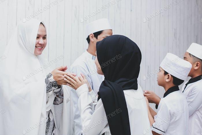 Muslim friend and family forgiving each other on eid mubarak