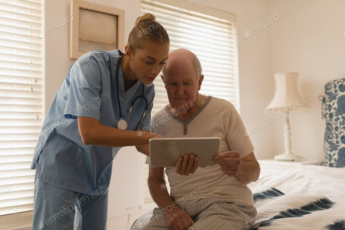 Female doctor using digital tablet and showing something to a senior man sitting on bedroom at home
