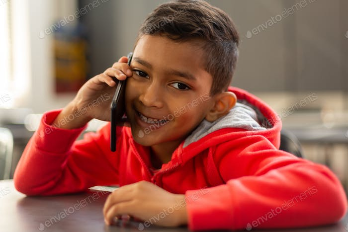 Smiling schoolboy talking on mobile phone at desk in a classroom at elementary school