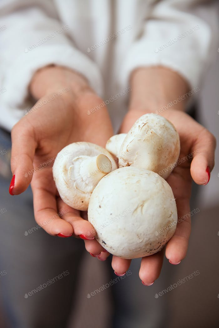 Young woman hands with mushrooms