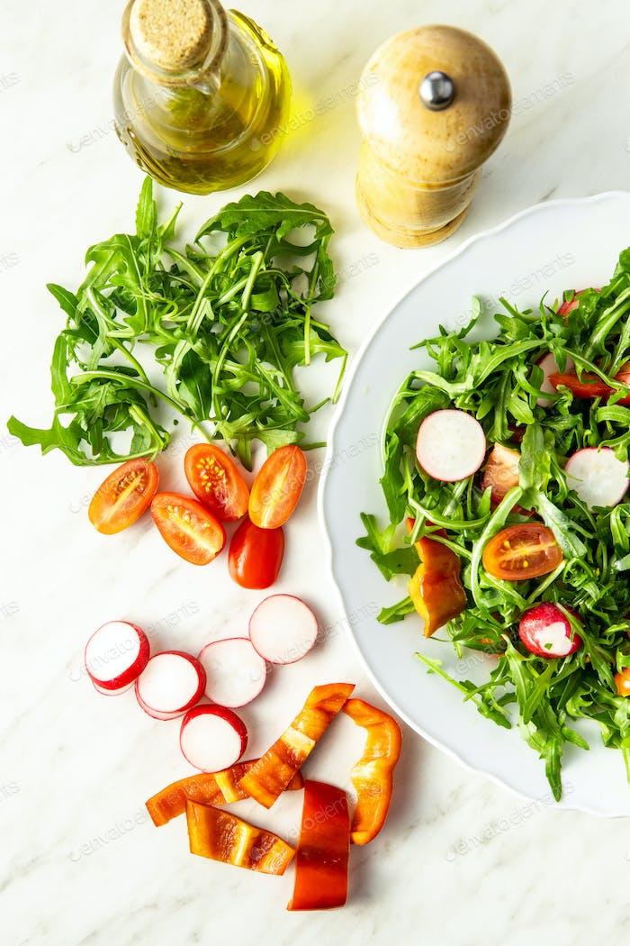 Frischer Rucola Salat mit Radieschen, Tomaten und Paprika.