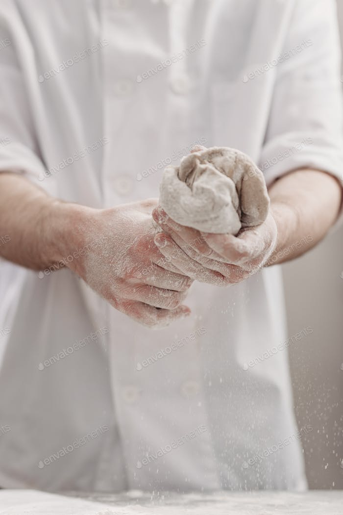Professional baker kneads dough in his hands in the kitchen of the bakery