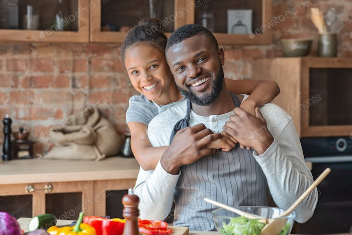 Thankful little girl embracing her daddy with love in kitchen