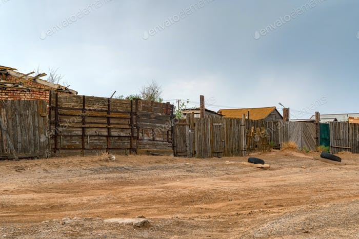 Houses in kalmyk village with a high wooden fence