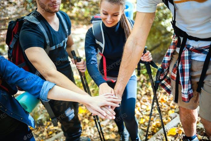 Gruppe von Freunden, die Hände stapeln, bevor sie auf dem Bergpfad steigen, Motivation beim Trekking