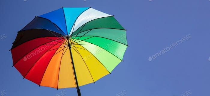 Umbrella rainbow colors on blue sky background, inside shot