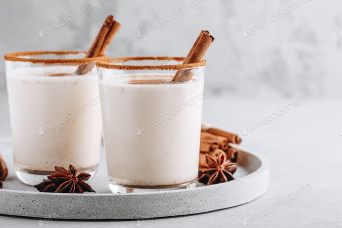 Homemade vanilla Christmas drink Eggnog in glass with grated nutmeg and cinnamon sticks