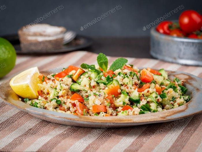 Tabbouleh salad with quinoa. Eastern food with vegetables mix, vegan diet. Side view