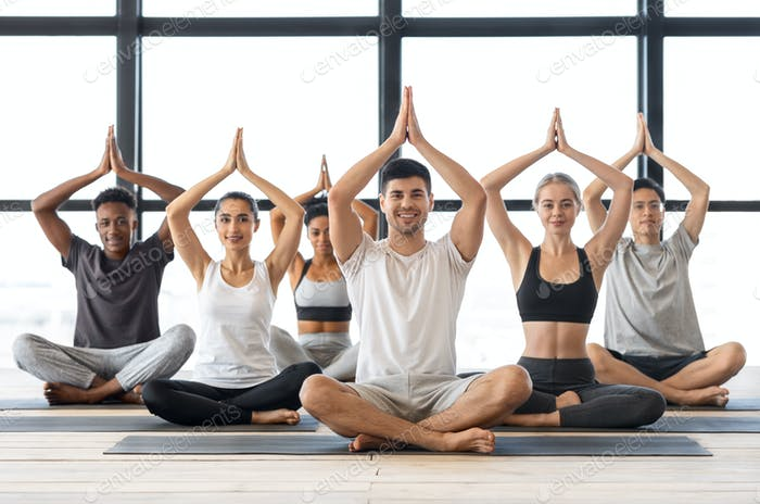 Wellbeing Concept. Happy multicultural people practicing group yoga in modern studio