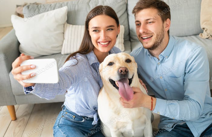 Young couple taking selfie with their dog at home