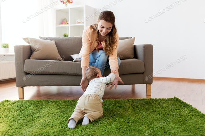 happy young mother playing with baby at home