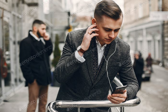 Two businessmen working with a phone