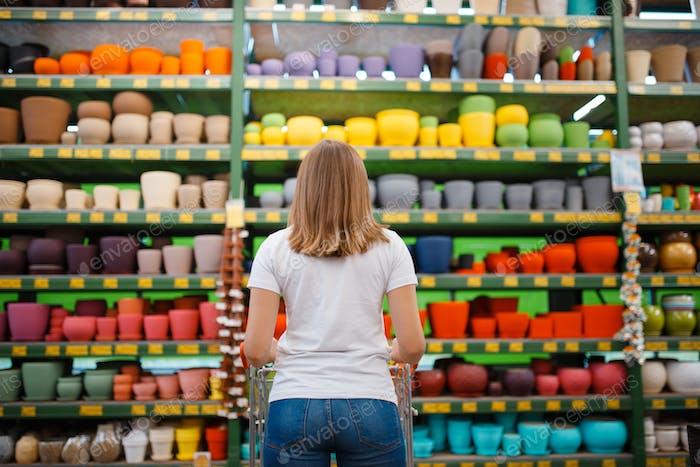 Женщина-клиент на полке с цветочными горшками