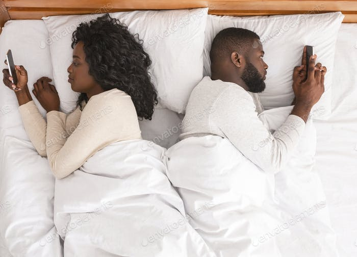Afro couple using smartphones in bed, ignoring each other after quarrel