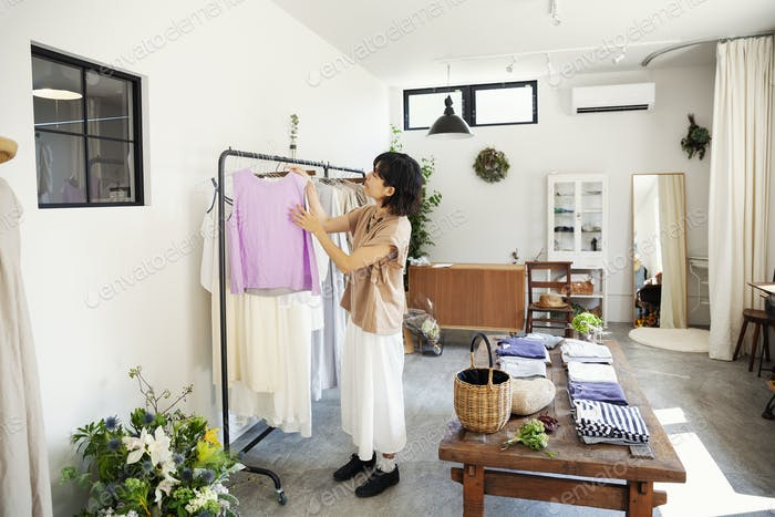 Japanese woman standing in a boutique, looking at clothes on a rail.