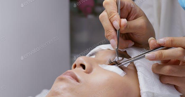 Schöne junge Frau mit Wimpernverlängerung im Salon
