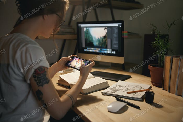 Woman designer sitting indoors at night play games