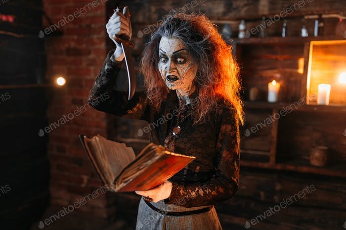 Scary witch holds spellbook and knife