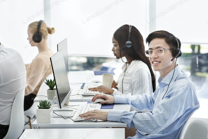 Group of positive technical support managers working on hotline at call centre