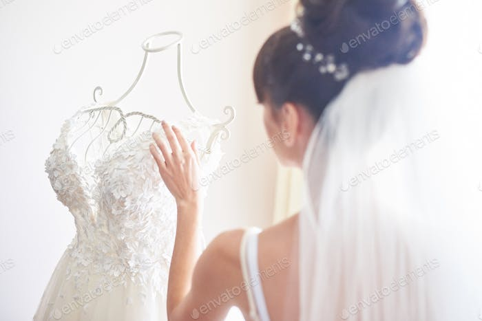 Elegant bride puts a wedding gown in her room