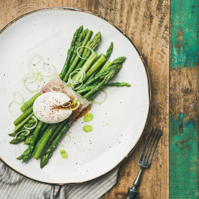 Green asparagus with soft-boiled egg in white plate, square crop