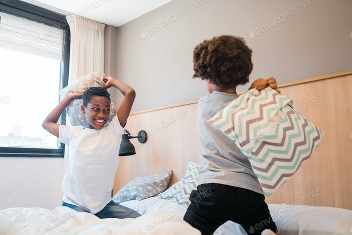 Two brothers playing with pillows at home.