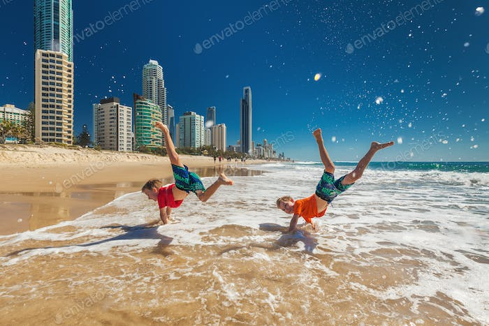 Two happy boys doing hand stands on Gold Coast beach, Australia