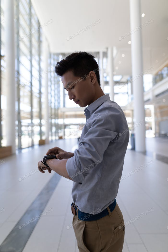 Rear view of young Asian male executive using smartwatch standing in modern office
