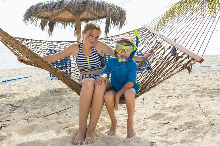 A teenage girl and her brother sitting on a hammock on the beach.