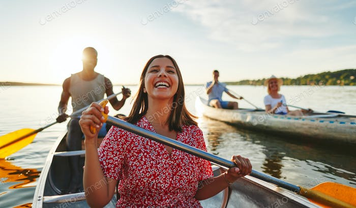 Young woman laughing while canoeing with friends in the summer