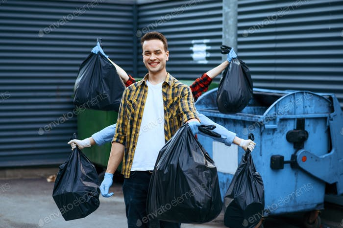 Funny volunteers shows plastic trash bags outdoors