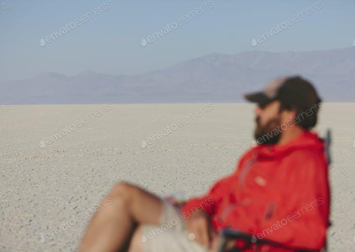 Mann sitzt im Stuhl in ausgedehnter, karger Wüste, verschwommener Fokus