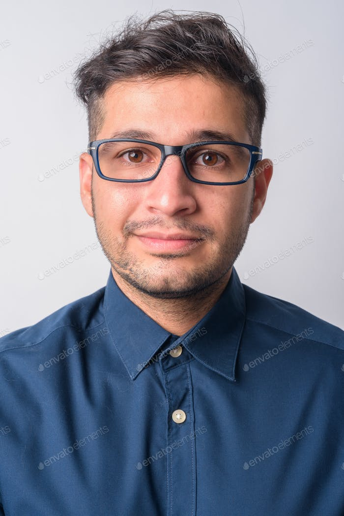 Face of young handsome Persian businessman wearing eyeglasses