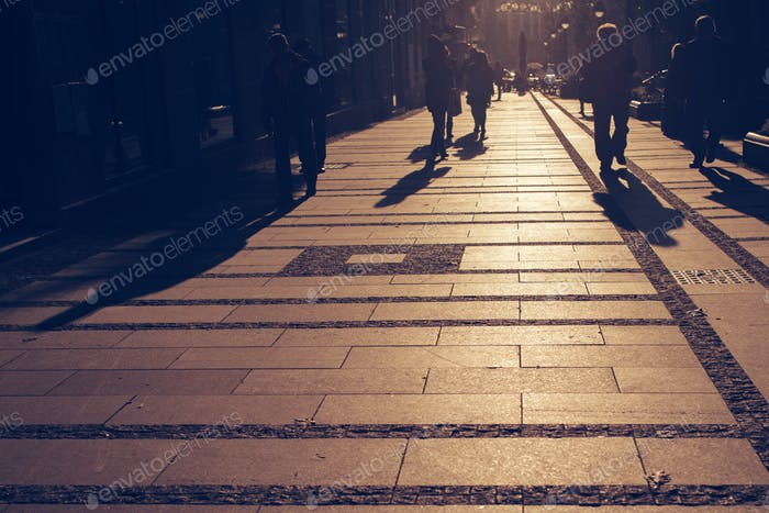 Silhouettes of people walking on city street