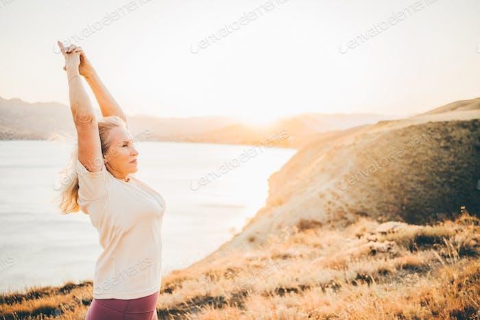 Woman practicing Yoga, meditation close to the sea.
