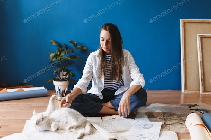 Beautiful girl sitting on floor with drawings dreamily playing w