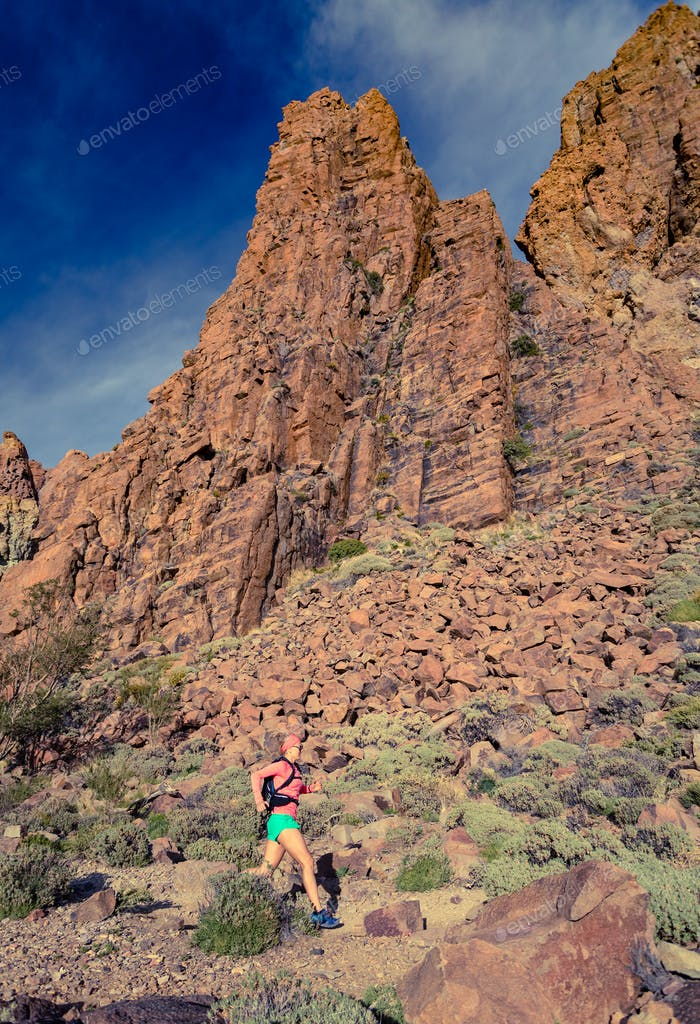 Woman running in inspirational mountains landscape